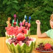 Little girl eats fruit in garden, happy birthday party seven yea - Stock Photo