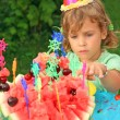 Little girl in cap eats fruit in garden, happy birthday - Stockfoto