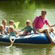 Children and adults float on an inflatable boat and fish a net. — Stock Photo