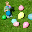 The boy inflates balloons, sitting on a grass — Stock Photo #7431244