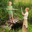 Stock Photo: Two boys with sticks battling for fun on bridges over stream