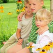 Children sitting on bench in garden — Stock fotografie #7431280
