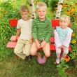 Children sitting on bench in garden — Stock Photo #7431284