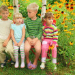 Children sitting on bench in garden — Stock Photo