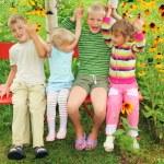 Children sitting on bench in garden, having joined hands — Stock Photo #7431289