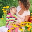 Young woman with little girl sitting on bench in garden — Stock Photo