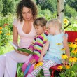 Young woman reads the book to two little girls in garden — Stock Photo #7431295