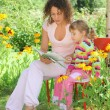 Young woman reads the book to little girl in garden — Foto Stock