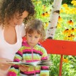 Stock Photo: Young woman reads the book to little girl in garden