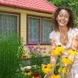 Young woman care of flowers in garden near house — Stock Photo