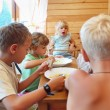 Children having dinner behind table — Foto Stock