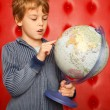 Royalty-Free Stock Photo: Boy pointing finger on globe. Portrait on red