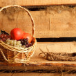 Stock Photo: Rural still life. Basket of grapes and apples, and bast shoes on