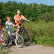 Mother with son and daughter ride bikes outside the city — Stock Photo #7431665