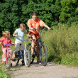 Stock Photo: Mother with son and daughter ride bikes outside the city