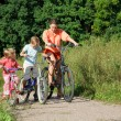 Mother with son and daughter ride bikes outside the city — Stock Photo