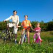 Parents with the daughter on bicycles in park a sunny day. Keep - Stock Photo