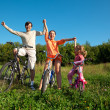 Parents with the daughter on bicycles in park a sunny day. Have — Stock Photo #7431671
