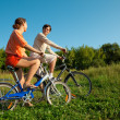The girl and the man go for a drive on bicycles in a sunny day — Stock Photo