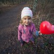 Little girl with heart-shaped baloon — Stock Photo #7431754