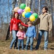 Parents with the daughter and the son walk in park with balloons — Stock Photo #7431870