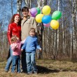 Parents with the daughter and the son walk in park with balloons - Stock Photo