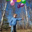 The boy with a sheaf of balloons in park in the spring — Stock Photo #7431877