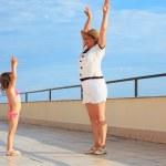 Elderly woman and little girl do morning exercise on veranda ne — Stock Photo