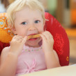 Pretty blond little girl eats bread, sitting in an armchair — Stock Photo #7432136