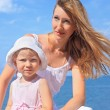 Beautiful woman with little girl in white hat near sea — Stock Photo #7432143