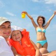 Young man with little girl in orange lifejacket and beautiful wo — Stock Photo