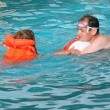 Young man and little girl in lifejacket bathing  in pool on reso - Stock Photo