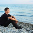 Sitting teenager boy on stone seacoast, Looking afar — Stock Photo