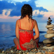 Beautiful woman in red sundress sitting near to pyramid from peb - Stock Photo