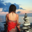 Beautiful woman in red sundress meditating near to pyramid from - 图库照片