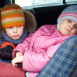 The sad boy with the little girl, in winter clothes in the car. — Stock Photo