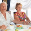 Stock Photo: Smiling elderly married couple having breakfast at restaurant ne