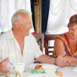 Smiling elderly married couple having breakfast at restaurant ne — Stock Photo