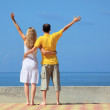Young man and beautiful woman on quay lifted hands upwards — Stock Photo