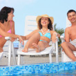 Smiling man and two young women reclining on chaise lounges near — Stock Photo