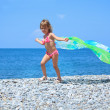 Pretty little girl with fabric on stony seacoast — Stock Photo #7432282