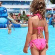 Little girl near pool in aquapark of an entertaining complex, st — ストック写真