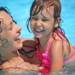 Smiling beautiful woman and little girl bathes in pool — Stock Photo #7432302