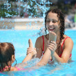 Smiling beautiful woman and little girl bathes in pool under wat — Stock Photo