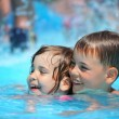 Smiling boy and little girl swimming in pool in aquapark — Stock Photo