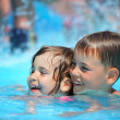 Smiling boy and little girl swimming in pool in aquapark — Stock Photo #7432310