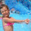 Little girl bathes in pool under water splashes in aquapark — Stock Photo