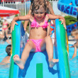 Stock Photo: Pretty little girl goes down on hill in aquapark of entertain