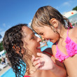 Smiling beautiful woman and little girl bathing in pool of an en — Stock Photo