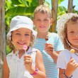 Smiling children three together eat lollipop in park — Stock Photo #7432357